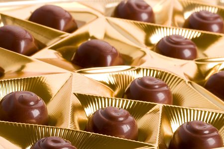 chocolate sweets in golden box closeup photo