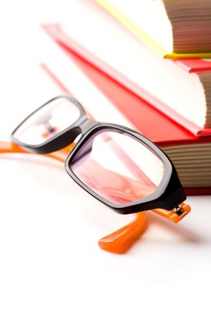 stack of books and glasses closeup on white background photo