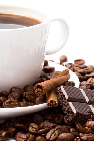 cup of coffee, beans, cinnamon and black chocolate closeup photo