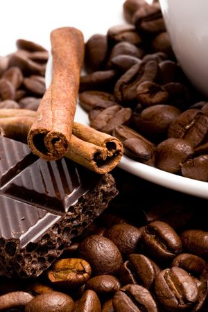 chocolate, coffee beans, cinnamon sticks and cup closeup photo