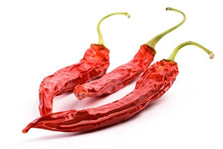 frutas deshidratadas: tres pimientos chilly rojos sobre fondo blanco en seco