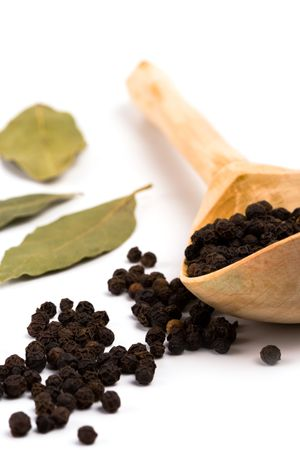 black pepper on wooden spoon and bay leaves on white background Stock Photo - 6284150