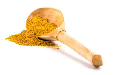 curry spices: pile of yellow turmeric on wooden spoon on white background