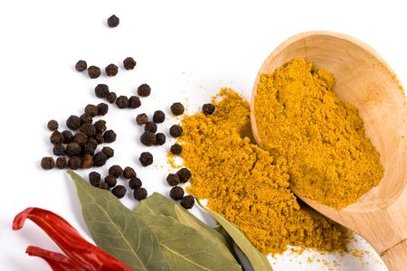 curry on wooden spoon, pepper, pimento and bay leaves on white background