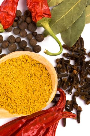 curry on wooden spoon, pepper, pimento, cloves and bay leaves on white background Stock Photo - 6309460