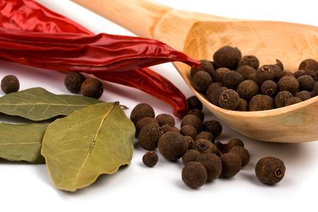 spices: bay leaves, pimento, aromatic pepper on wooden spoon closeup photo