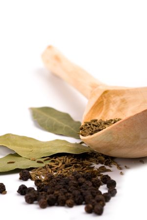 spices:  cumin on wooden spoon, black pepper and bay leaves on white background Stock Photo - 6349666