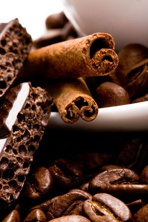 macro image of cup of coffee, cinnamon, beans and black chocolate photo