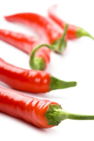 five red chili peppers closeup on white background photo
