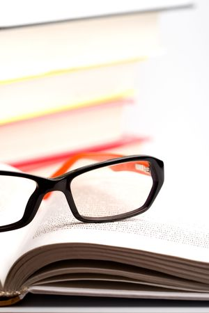 books and glasses closeup on white background photo