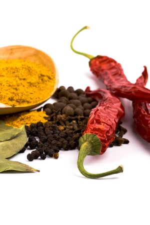 pimento: spices: curry on wooden spoon, pepper, pimento, cloves and bay leaves on white background