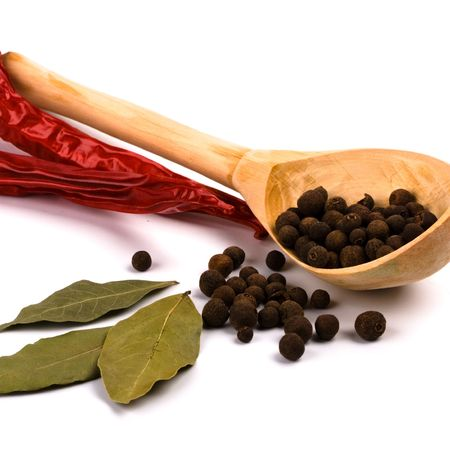 pimento: spices: bay leaves, aromatic pepper in wooden spoon, pimento closeup on white background
