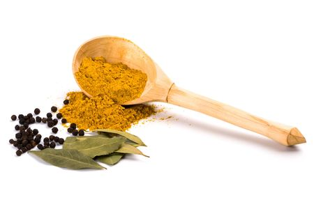 spices: curry on wooden spoon, pepper, bay leaves isolated on white background photo