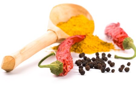 spices: pepper, pimento, curry on wooden spoon closeup on white background photo
