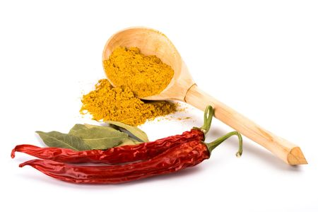 spices: curry in wooden spoon, chili pepper and bay leaves on white background photo