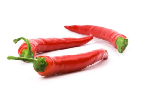three red chili peppers on white background photo