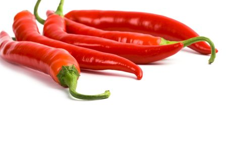 five red chilli peppers closeup on white background