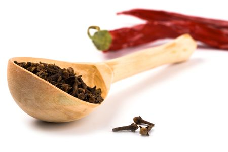 spices: cloves in wooden spoon and pimento closeup on white background photo