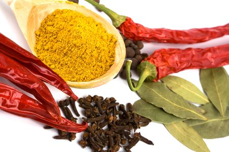 spices: curry in wooden spoon, pepper, pimento, cloves and bay leaves closeup on white background photo