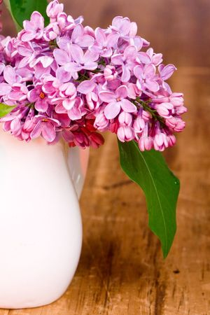 lilac blooms in small white vase on wooden table Stock Photo - 6971868