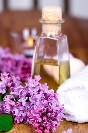 bath and spa items (towel, oil, lilac, candle) on wooden background photo