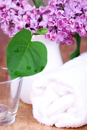 rolled towel, lilac and candle closeup on wooden background Stock Photo - 6971892