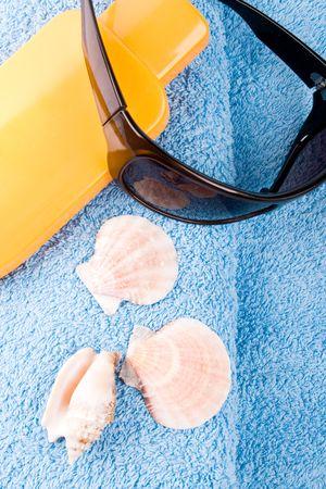 towel, sunglasses and lotion closeup photo