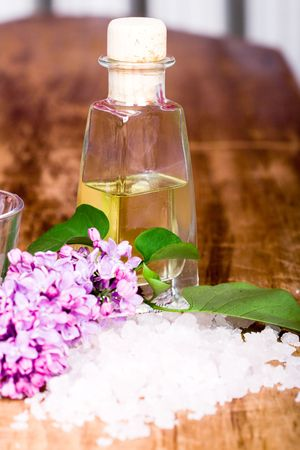 bath and spa items (salt, oil, lilac) on wooden background photo