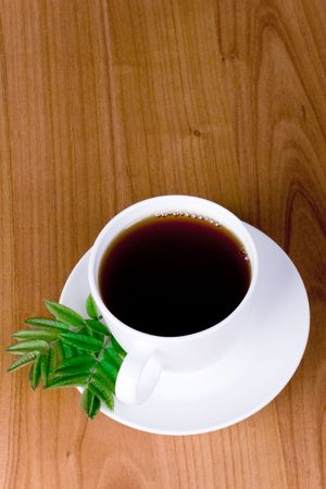 cup of black tea with herbs on wooden background photo