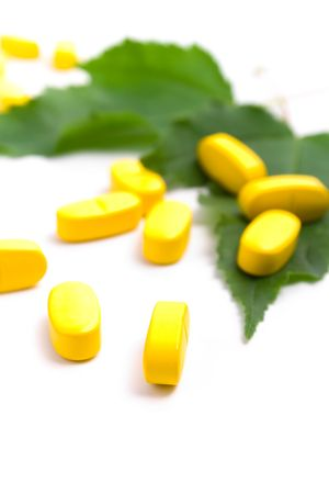 yellow vitamin pills over green leaves on white background Stock Photo - 7074047