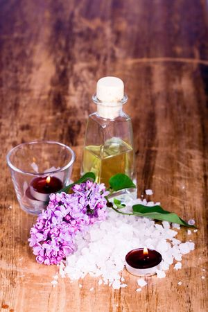 bath and spa items (oil, salt, lilac, candle) on wooden background photo