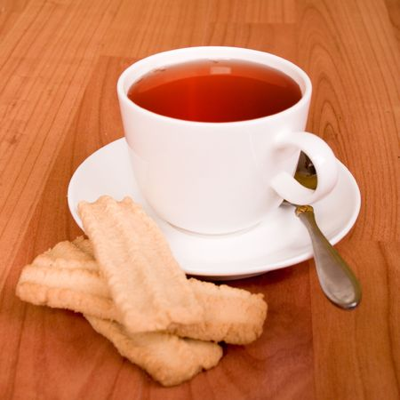 cup of tea and some cookies on wooden table photo
