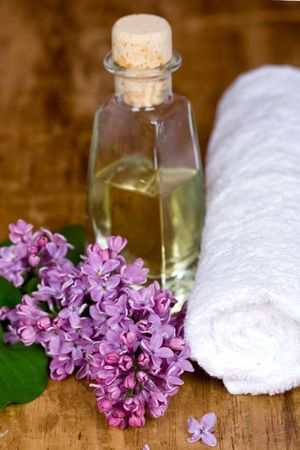 bath and spa items (towel, oil, lilac) on wooden background photo