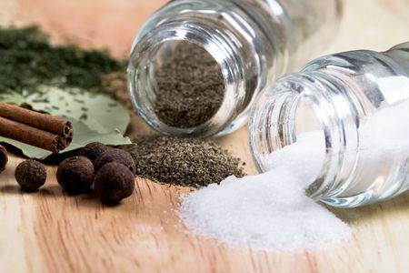 pepe nero: spezie: sale, foglie di alloro, pepe, cannella ed erbe alzato su fondo in legno