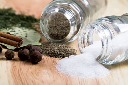spices: pepper, salt, bay leaves, cinnamon and herbs closeup on wooden background