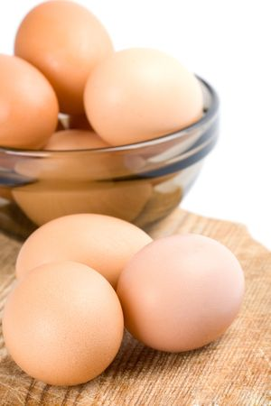 brown eggs in a bowl on a wooden board photo
