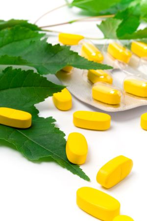 yellow vitamin pills and green leaves on white background