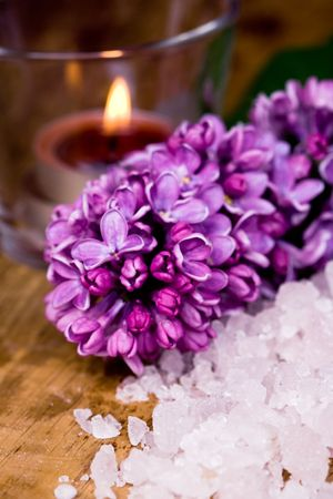 scented candle: lilac, bath salt and candle closeup on wooden background