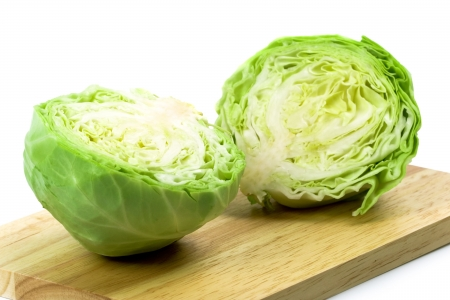 two halves of green cabbage on wooden chopping board photo