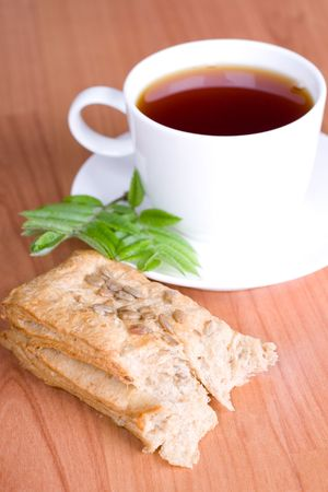 cup of black tea with herbs and bread on wooden background photo