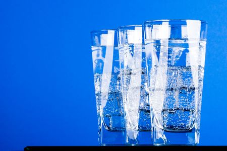 three glasses with cold water on blue background Stock Photo - 7207982