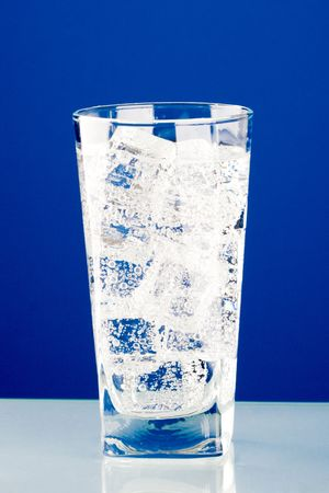glass with cold water and ice on blue background photo