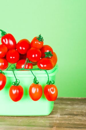 container with fresh tomatoes closeup on green background Stock Photo - 7208042