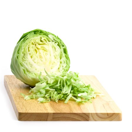 savoy cabbage: green cabbage shredded on wooden chopping board isolated on white background Stock Photo
