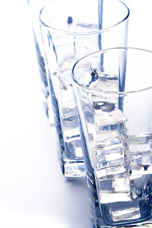 three glasses with ice cubes closeup on white background photo