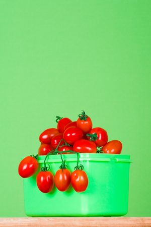 container with fresh tomatoes on green background photo