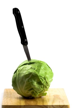 green cabbage with knife on wooden chopping board isolated on white background photo