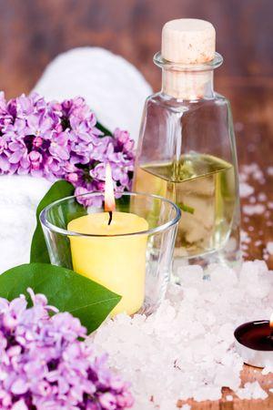 artículos de baño y spa (toalla, sal, aceite, lila, vela) sobre fondo de madera
