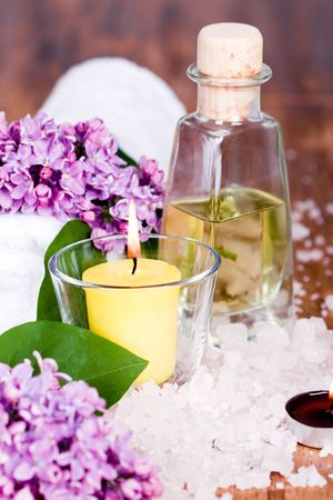 violeta: artículos de baño y spa (toalla, sal, aceite, lila, vela) sobre fondo de madera