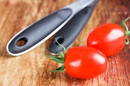 two fresh tomatoes and spoons on wooden background photo